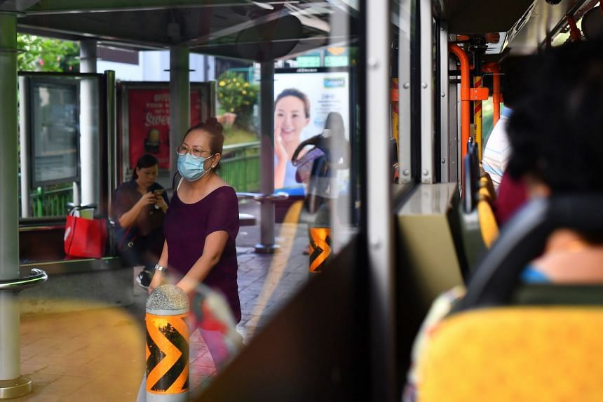 A woman wears a protective face mask at a bus stop in Bedok on March 24, 2020.