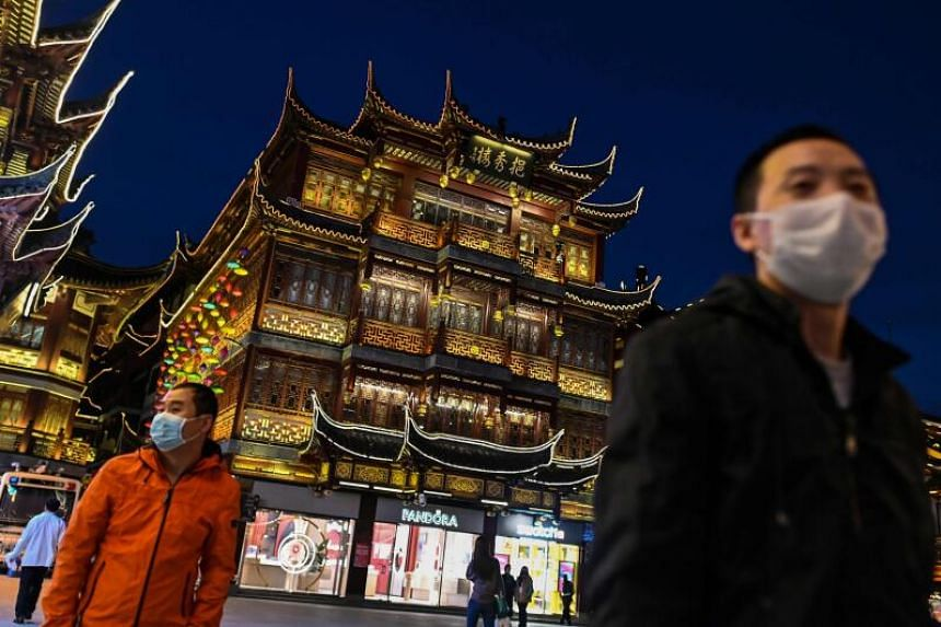 People wearing face masks as a preventive measure against the Covid-19 coronavirus visit the Yu Garden in Shanghai, on March 23, 2020.