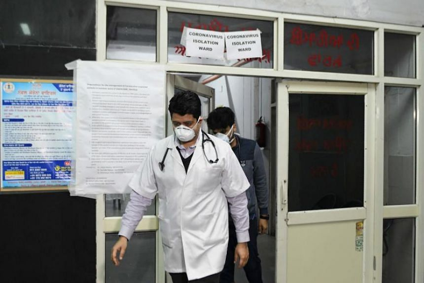 Doctors are seen in front of an isloation ward for coronavirus patients at Guru Nanak Dev hospital in Amritsar, India, on March 7, 2020.