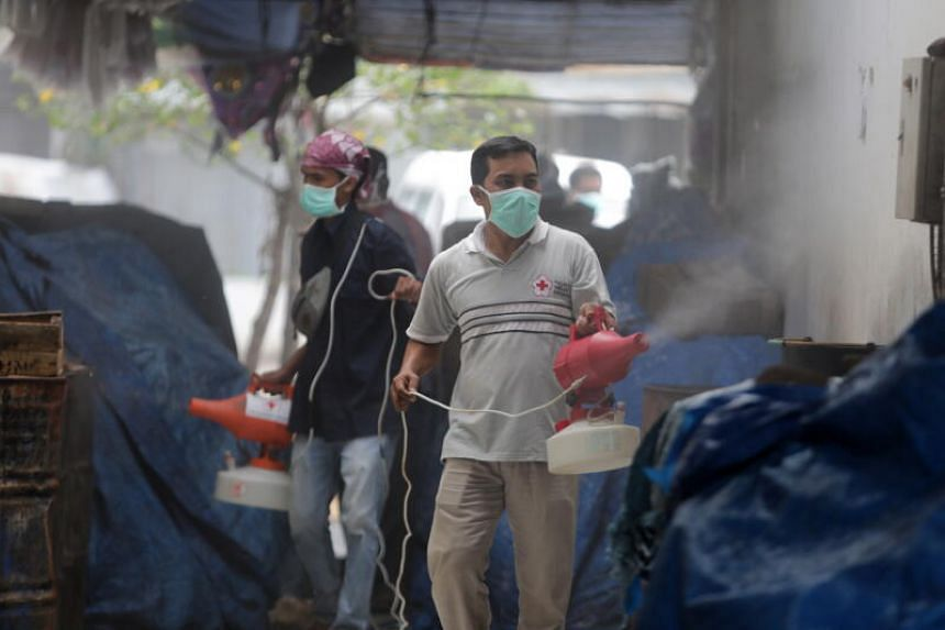 An Indonesian official sprays disinfectant at a traditional market in Aceh Besar Regency, Indonesia, on March 25, 2020.