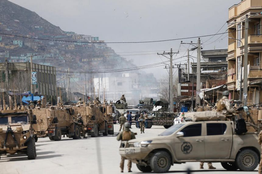 Afghan security forces inspect the area near the site of an attack in Kabul, on March 25, 2020.