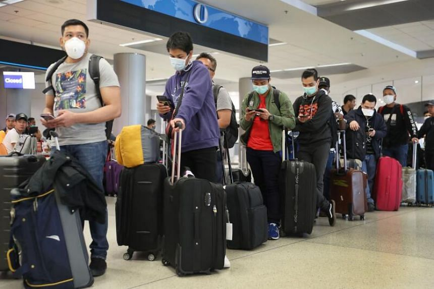 A photo taken on March 15, 2020 shows travellers waiting to check in at Miami International Airport.