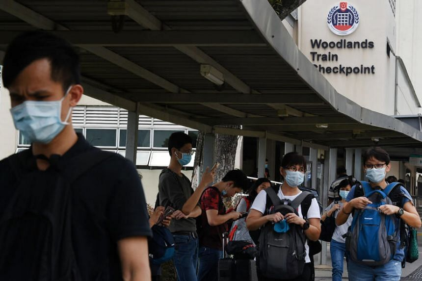 People with face masks at Woodlands checkpoint in Singapore on March 17, 2020. Singapore and Malaysia have agreed on applying the same cut-off of 37.5 deg C for the definition of travellers with a fever.