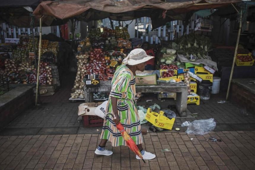 A woman walks by a food stall at an open air market in Kliptown, Soweto, on March 24, 2020. African finance ministers agreed that the continent needs a stimulus package of US$100 billion to face the new virus.