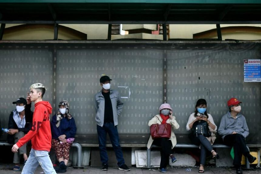 People with masks wait at a bus stop in Hanoi, on March 16, 2020.
