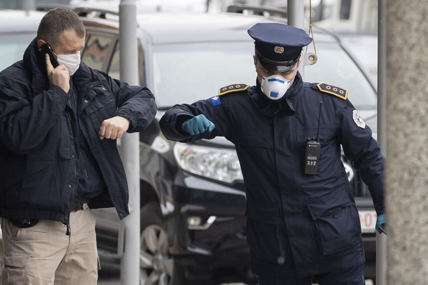 Kosovo police officers wearing face masks greet each other while on patrol in front of the parliament building in Pristina, March 25, 2020.