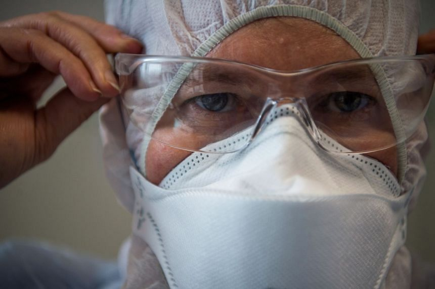 A medical staff member puts on protective gear before entering an isolation room at a Covid-19 care unit in Budapest, March 25, 2020.