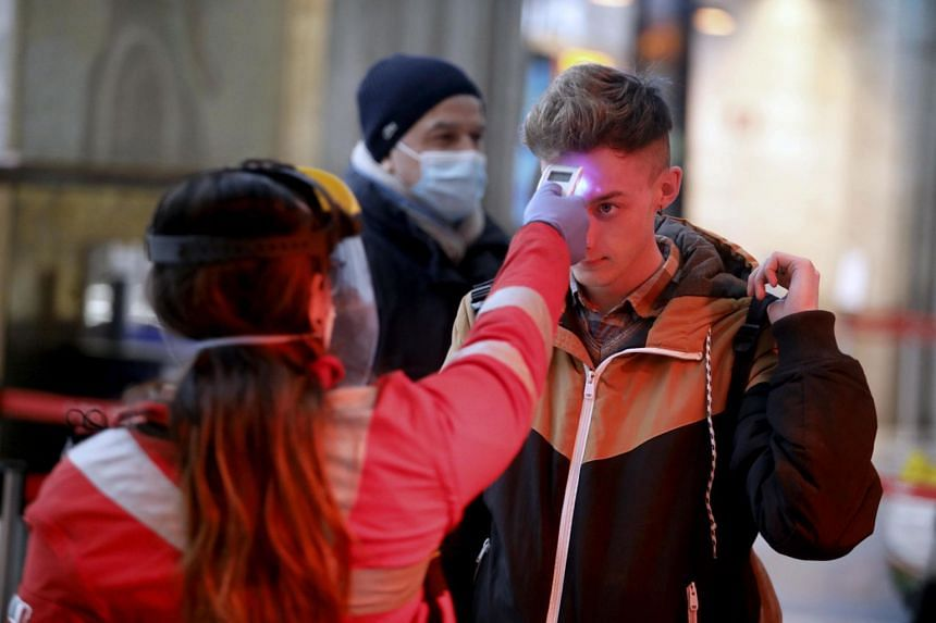People are checked for their temperatures at Milan Central Station, March 25, 2020.