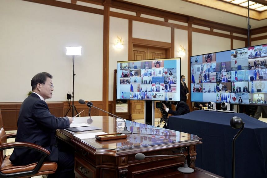 President Moon Jae-in (left) speaking with other G-20 leaders during the  special teleconference summit.