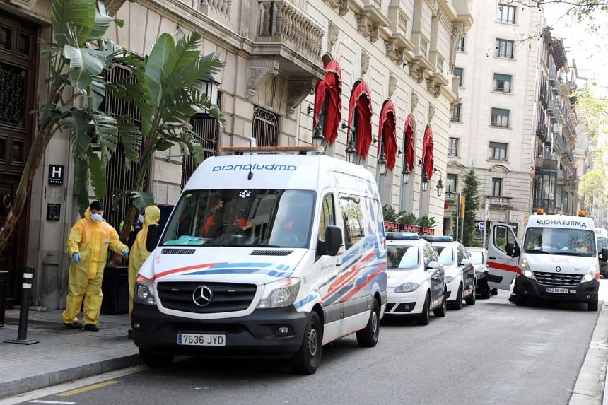 Ambulances and medical workers are seen outside a hotel in Barcelona prepared to host patients with mild coronavirus symptoms.