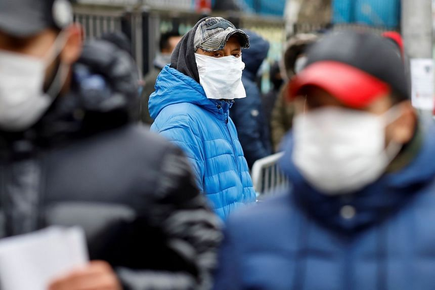 People wait to be tested for coronavirus in the Queens borough of New York City, March 25, 2020.