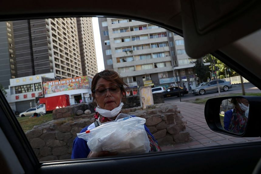 A woman sells protective face masks at a traffic light corner in Santiago, Chile, on March 24, 2020.