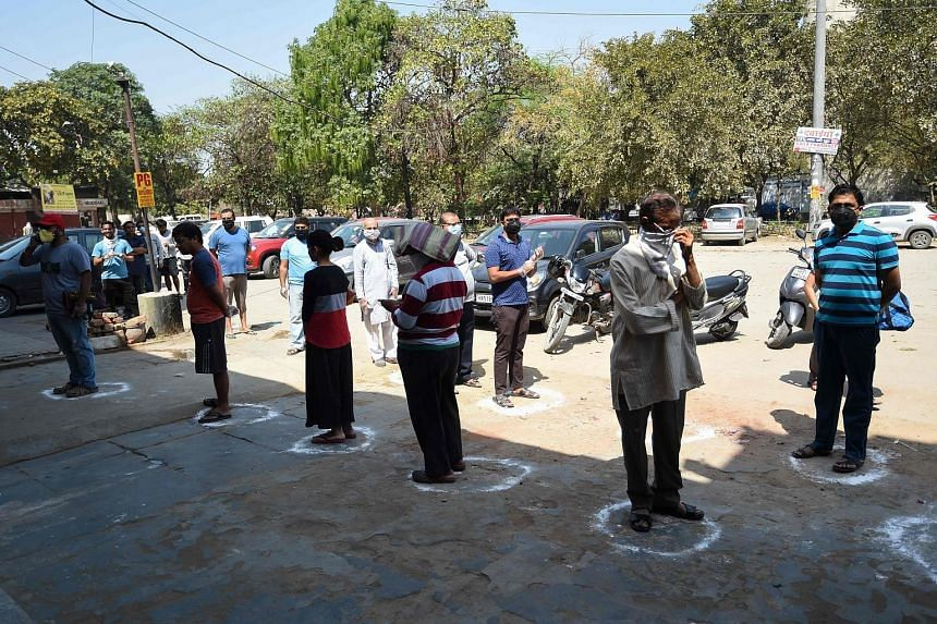 People queueing in designated spots at a grocery store in Faridabad yesterday, the first day of India's nationwide lockdown.