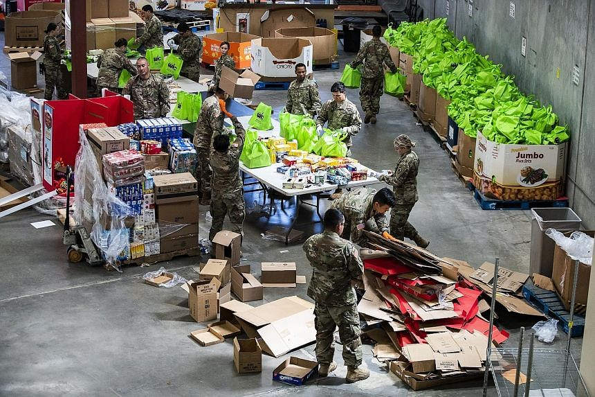 Soldiers packing donated food into bags that will be delivered to people in need at a food bank in Indio, California. The US' coronavirus relief package is expected to include a one-time direct payment of US$1,200 (S$1,730) per adult and US$500 per c