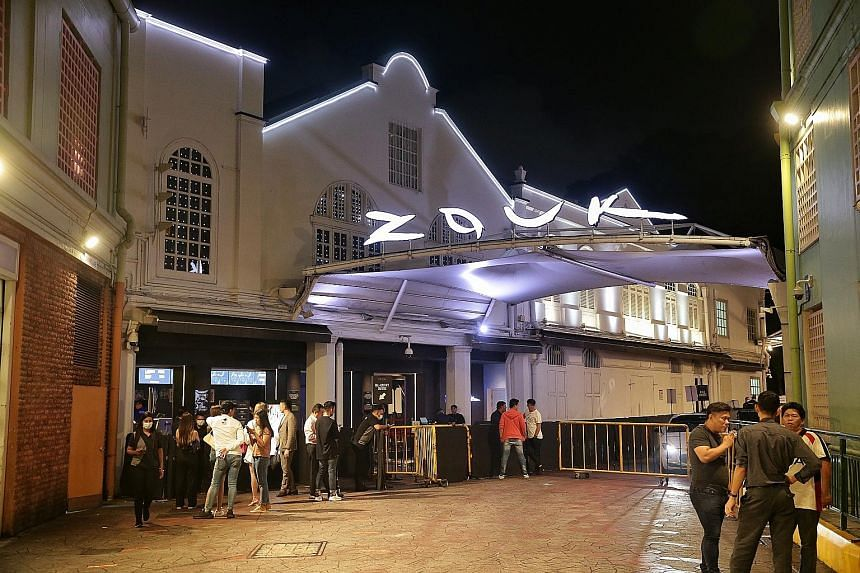 Club-goers did not have to wait long to enter popular nightclubs like Zouk (above), while at Le Noir (left), a bar at Clarke Quay, only a handful of patrons were spotted. ST PHOTOS: KEVIN LIM