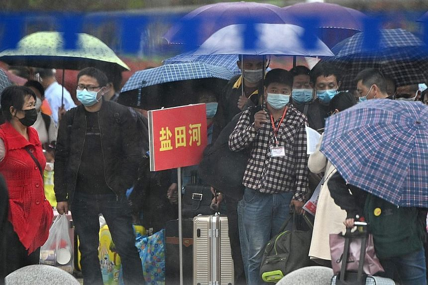 People queueing to buy tickets at the railway station in Macheng, in China's central Hubei province, yesterday. Strict curbs on daily life are finally being lifted, allowing healthy people to head home and see their loved ones after weeks of separati