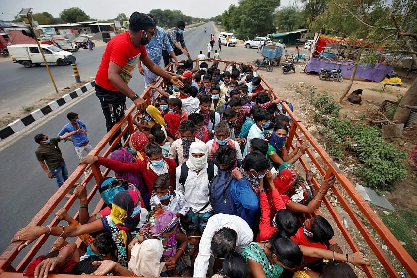 People practising social distancing while queueing outside a medical store in Allahabad yesterday. PHOTO: AGENCE FRANCE-PRESSE Migrant workers and their families boarding a truck to return to their villages yesterday after the lockdown in Ahmedabad.