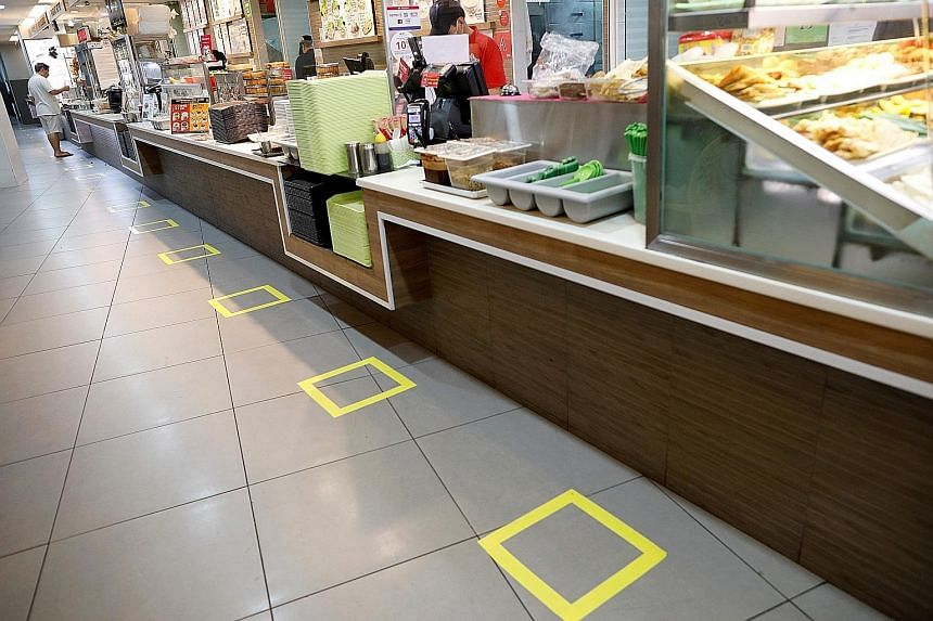 Social distancing markers outside Tangs department store in Orchard Road. Malls can stay open but have to abide by stricter precautions. Diners observing social distancing at a fast-food restaurant at Junction 8 mall yesterday. The lunchtime crowd at