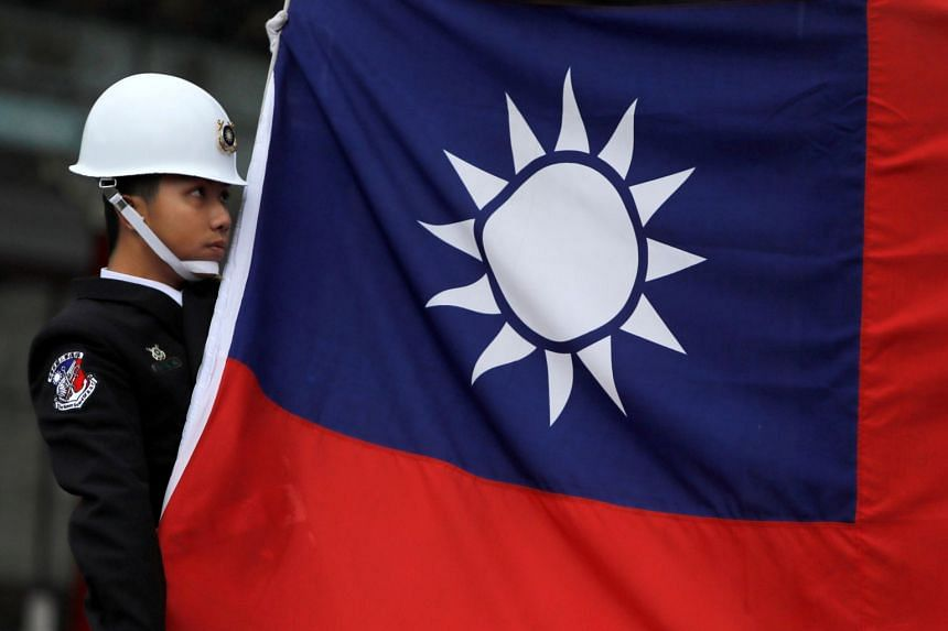 A military honour guard holds a Taiwanese national flag in Taiwan on March 16, 2018. The ship sailed north through the waterway and was monitored by Taiwan's armed forces.