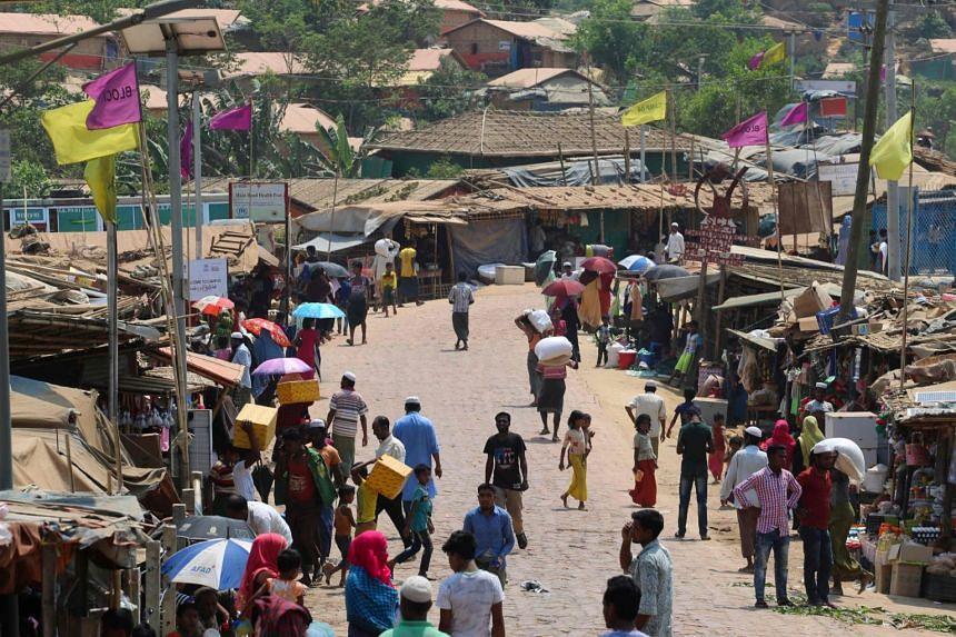 Rohingya refugees gather along a market area in Kutupalong refugee camp in Ukhia, Bangladesh, on March 24, 2020.