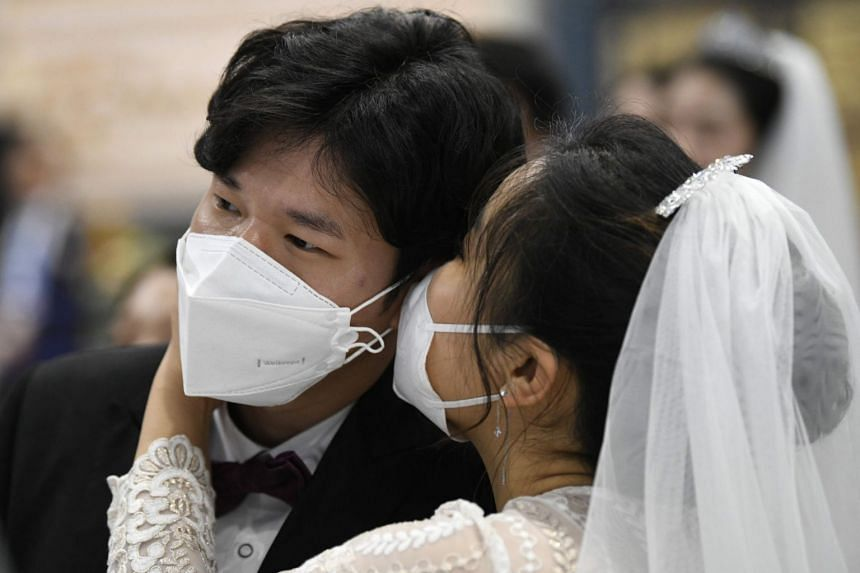 In a photo from Feb 7, 2020, a couple wearing protective face masks attend a mass wedding ceremony in Gapyeong, South Korea.