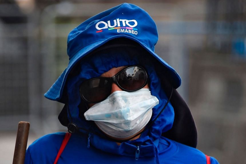A municipal worker sweeps the streets in the historic centre of Quito, on March 25, 2020.