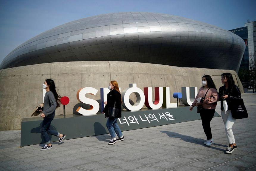 People wearing masks walk along a street in Seoul on March 25, 2020.