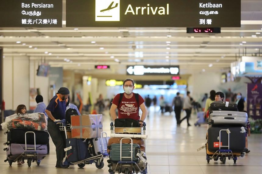 Travellers at Changi Airport Terminal 2 on March 24, 2020. Of the 52 new Covid-19 cases announced by the Ministry of Health on March 26, 28 were imported.