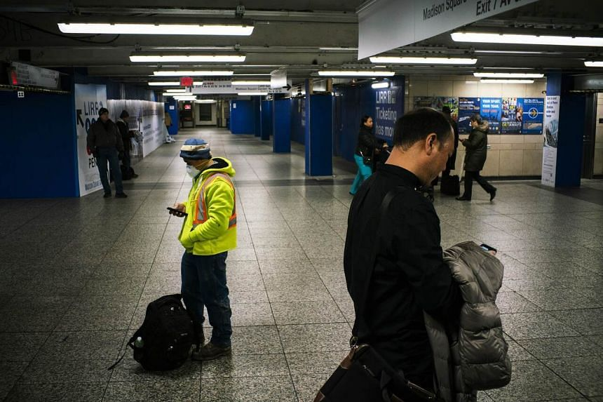 A man wears a face mask as people walk around of an almost empty Pennsylvania Station in New York City, US, on March 25, 2020.