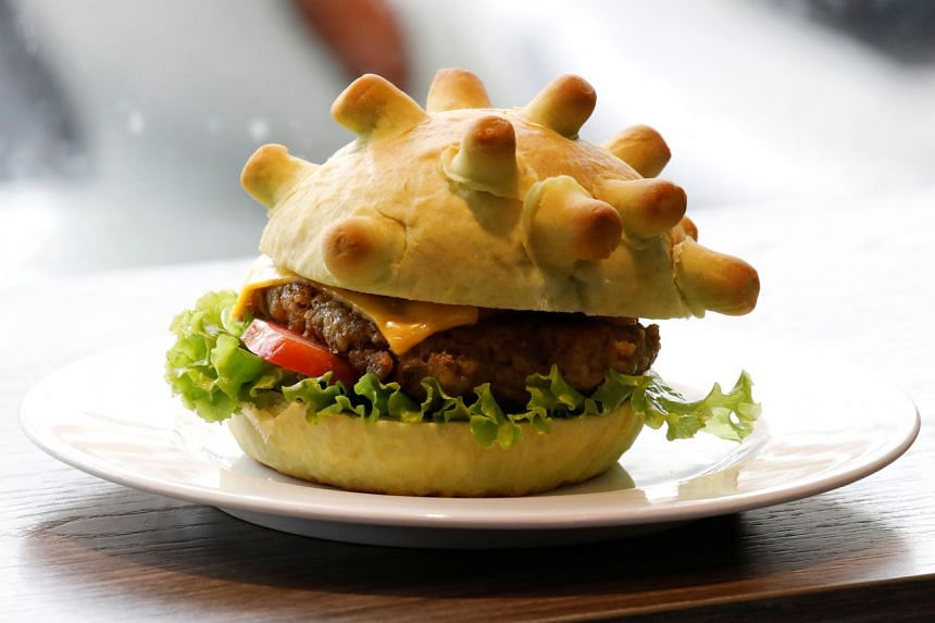 """The green-tea stained burger buns has little """"crowns"""" made of dough to resemble microscopic images of the virus."""