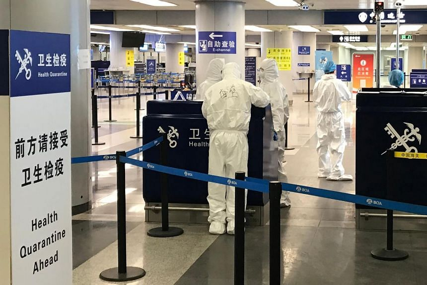 A photo taken on March 21, 2020, shows staff wearing protective suits at the health check counter in the international departures area of Beijing airport.
