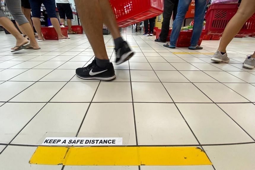 Yellow lines are placed about one metre apart at checkout counters at the NTUC Fairprice outlet at Jurong Point on March 21, 2020.