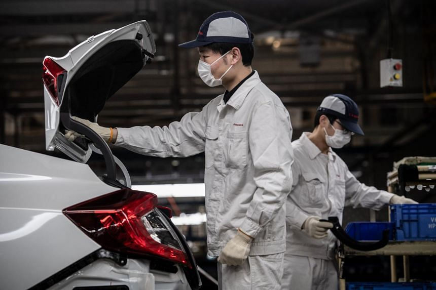 A photo taken on March 23, 2020, shows employees wearing face masks working on an assembly line at an auto plant of Dongfeng Honda in Wuhan.