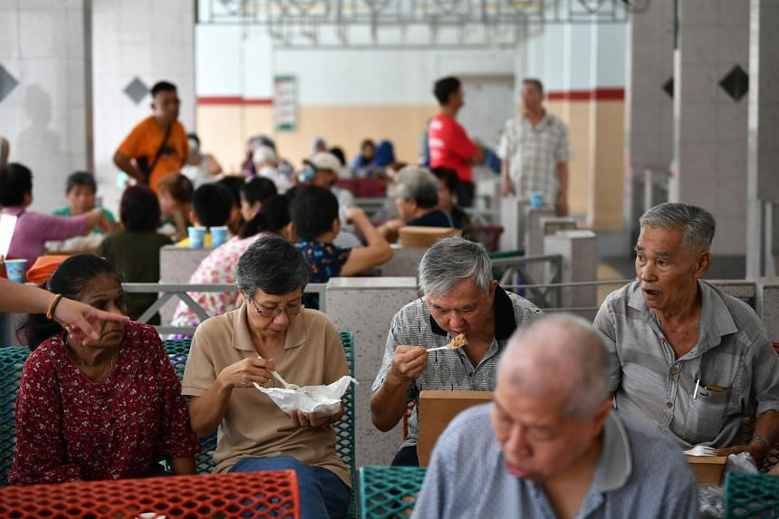In a photo from Dec 18, 2019, older people have their lunch at the void deck of a HDB block in Ang Mo Kio.