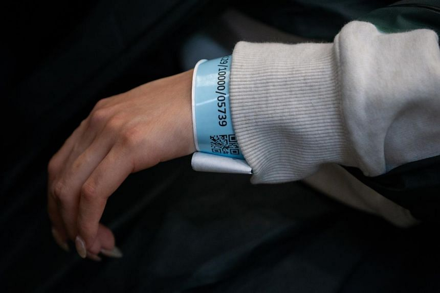 A traveller wears a wrist band to track her movement in the arrival hall of Hong Kong International Airport on March 19, 2020.