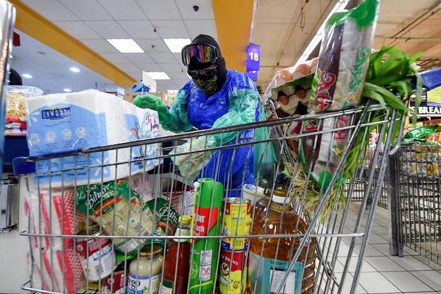 Engineer Zamakhyari Khariri wearing his self-made plastic bag suit while doing his grocery run at a supermarket in Terengganu, Malaysia.