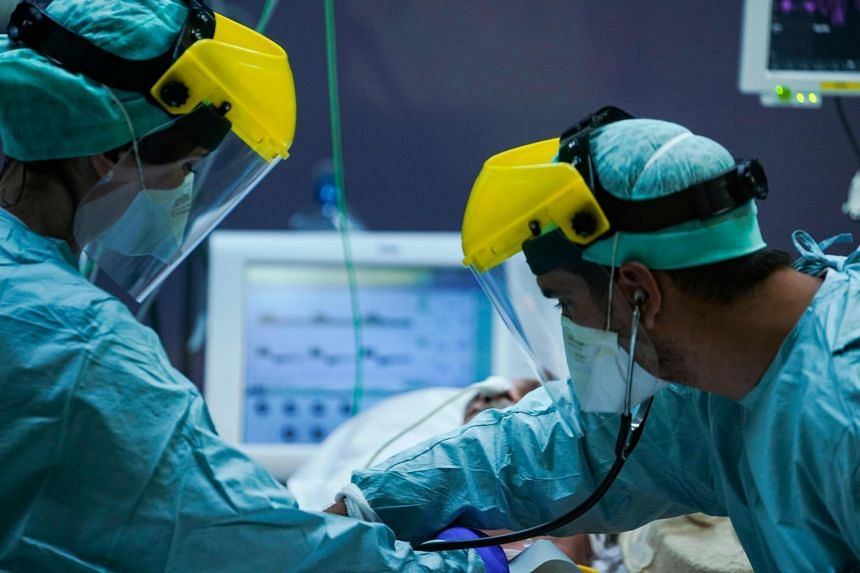 Medical workers wearing protective gears at the level intensive care unit at Erasme Hospital in Brussels, Belgium, on March 25, 2020.
