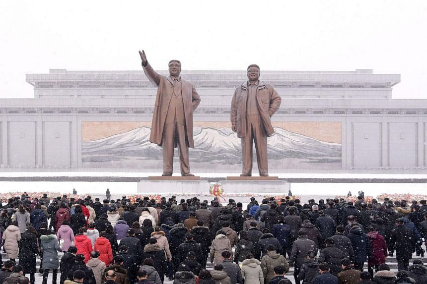 People standing in front of statues of late North Korean leaders Kim Il Sung and Kim Jong Il in Pyongyang, North Korea, on Feb 16, 2020.