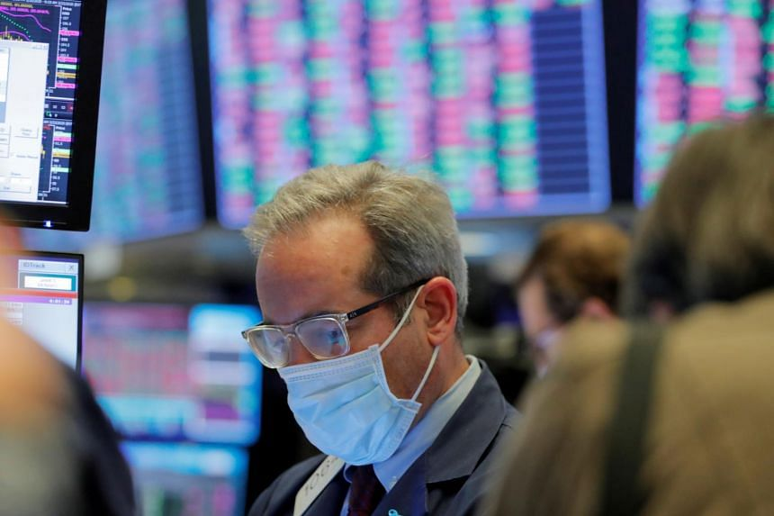 In a photo from March 20, 2020, a trader wears a mask as he works on the floor of the New York Stock Exchange as the building prepares to close indefinitely.