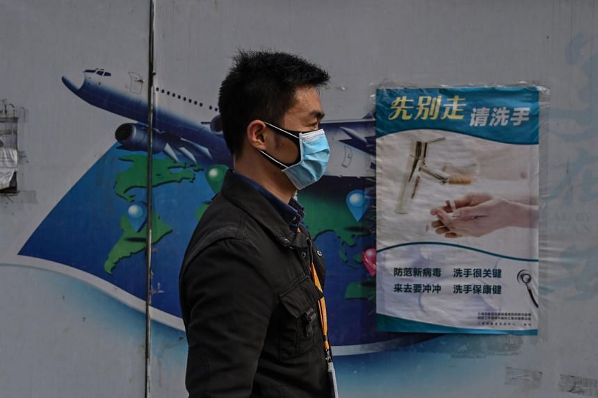 A man wearing a face mask walks on a street in Shanghai, China, on March 16, 2020.