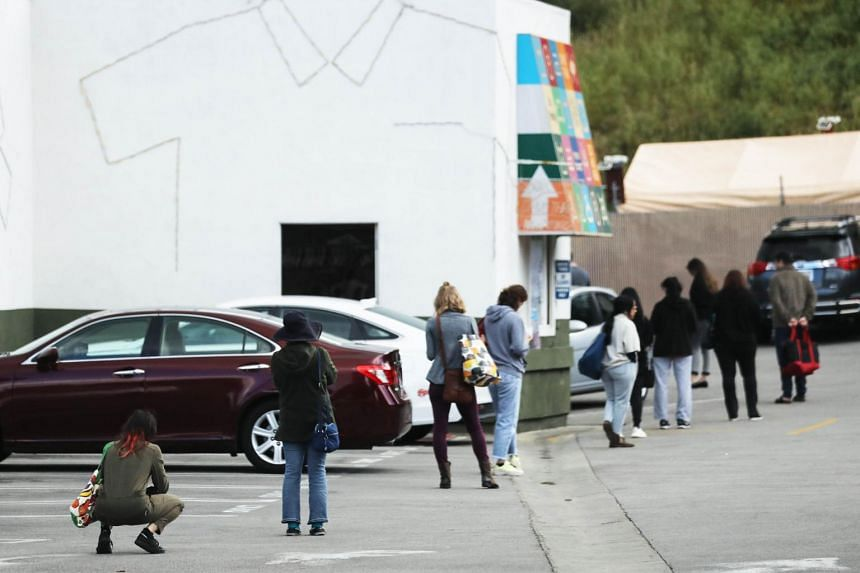 People maintain social distancing while standing in line to enter a Trader Joe's in Los Angeles, US, on March 25, 2020.