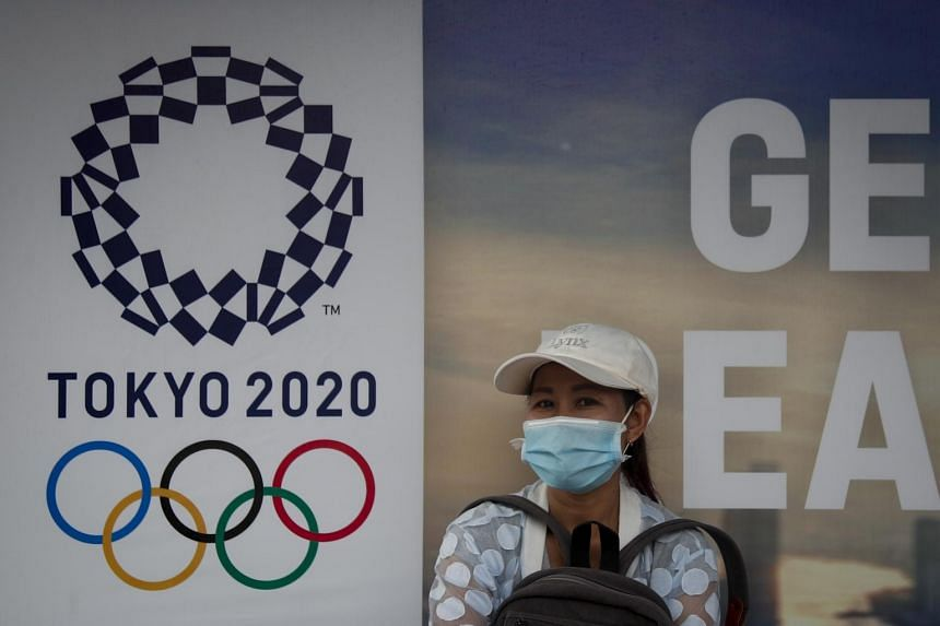 A woman wearing a protective face mask waits for a bus in front of a sign promoting the Tokyo Olympics at a bus stop in Bangkok, Thailand, on March 20, 2020.