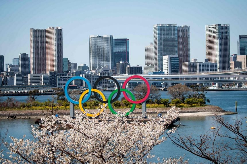 Cherry blossoms are seen near the Olympic rings in Tokyo's Odaiba district on March 25, 2020.