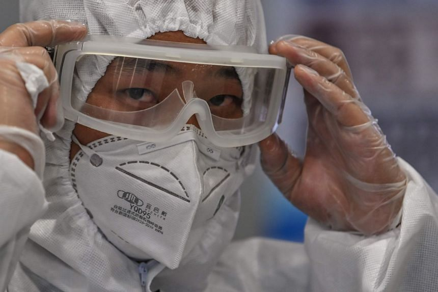 A member of airport security wearing protective gear monitors passengers on arrival at Shanghai Pudong International Airport on March 26, 2020.