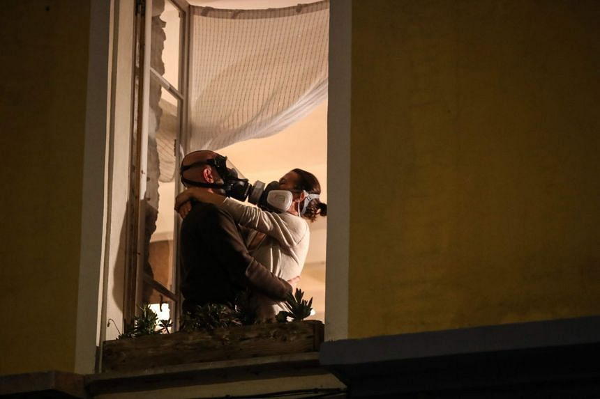 A man wearing a gas mask and a woman wearing an air filtering mask embrace at their window in the French Riviera city of Nice, on March 24, 2020.