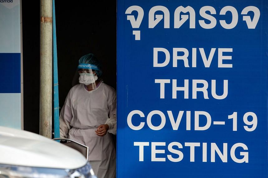 A medical staff member works at a drive-through coronavirus test centrel in Bangkok on March 25, 2020.