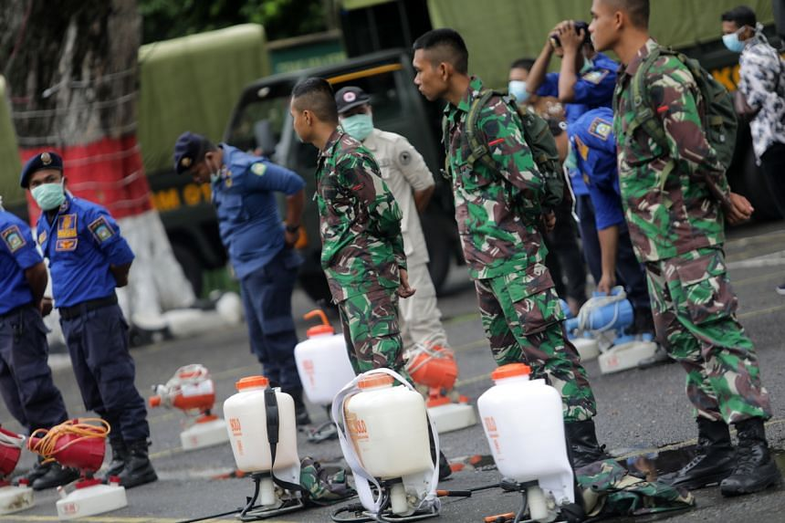 Authorities prepare to spray disinfectant in public areas, in an effort to stop the spread of the coronavirus in Banda Aceh, Indonesia, on March 26, 2020.