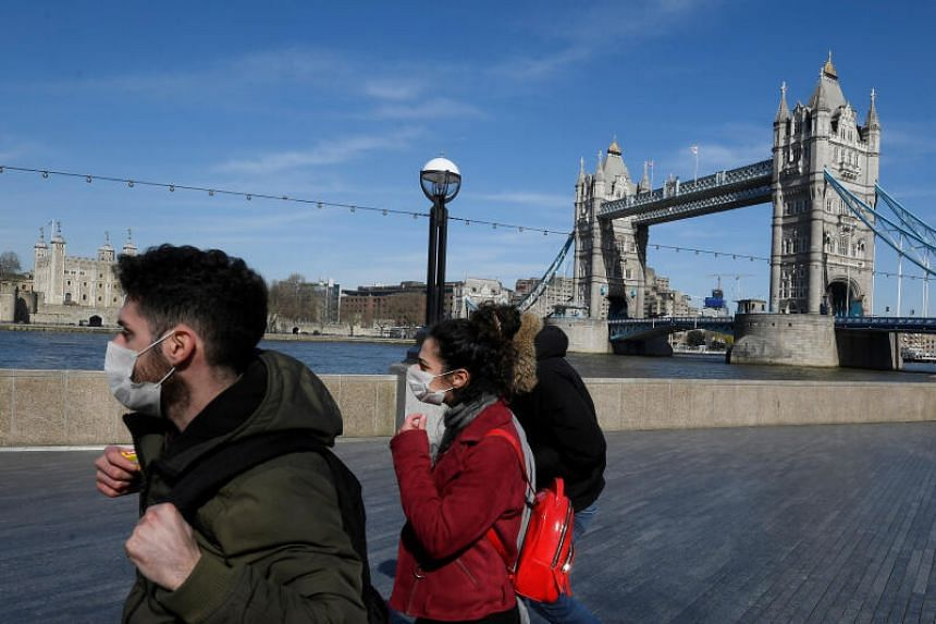 People with masks in front of Tower Bridge in London on March 23, 2020. Britain's Director of Public Prosecutions said people responsible for coughing in the faces of police, emergency workers and shop staff could face charges of common assault.