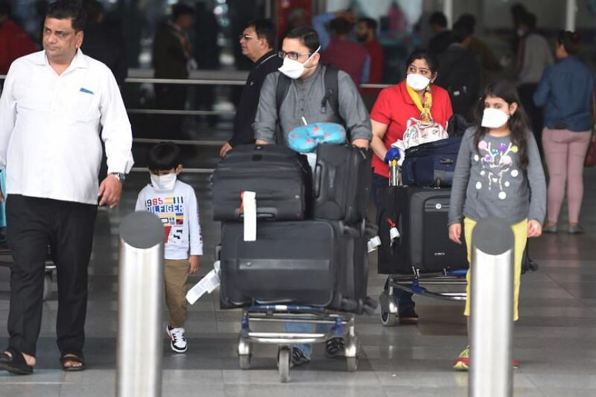 A photo taken on March 16, 2020 shows passengers with face masks outside the Indira Gandhi International Airport in New Delhi.