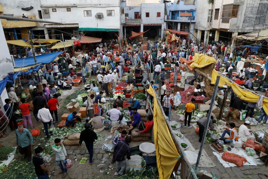 A photo taken on March 26, 2020 shows people in a market during a 21-day nationwide lockdown in the old quarters of New Delhi.